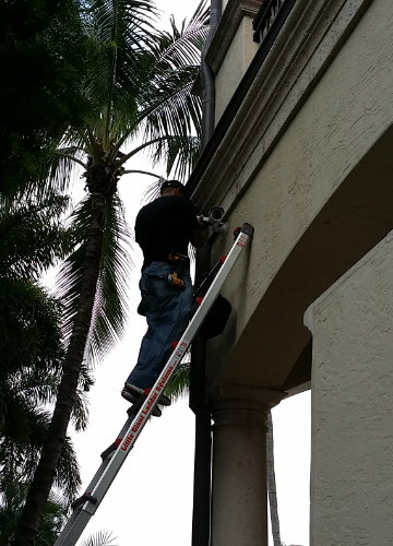 security camera installer on a ladder installing a camera